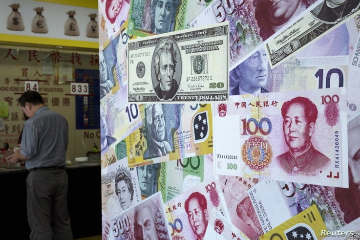 FILE - A customer is served at a counter at a foreign exchange store in Hong Kong, China, Aug. 13, 2015.