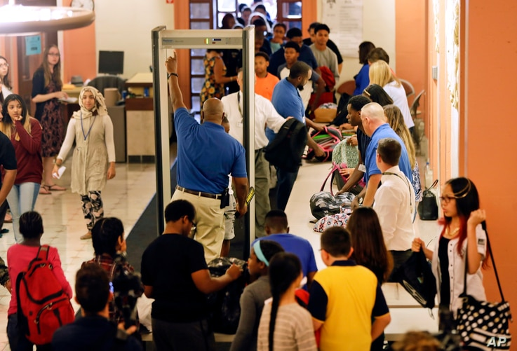 In this Sept. 6, 2016, photo, students at William Hackett Middle School have their bags checked and pass through metal detectors on the first day of school in Albany, New York.