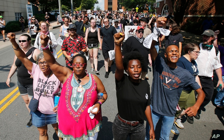 Demonstrators against racism march along city streets as they mark the anniversary of last year's Unite the Right rally in Charlottesville, Va., Sunday, Aug. 12, 2018.