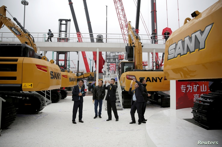 FILE - People visit heavy machinerys of Sany at Bauma China 2016, The 8th International Trade Fair for Construction Machinery in Shanghai, China, Nov. 22, 2016.