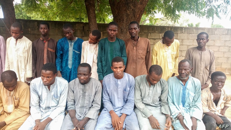 Police officers present suspected Boko Haram militants in Maiduguri, northest Nigeria, on July 18, 2018.