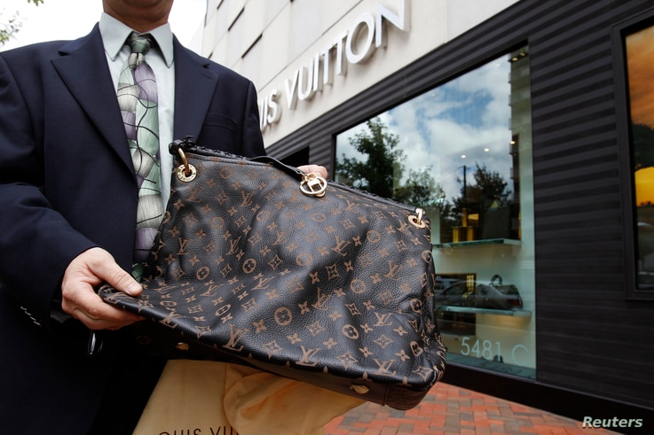 FILE - A fake LVMH handbag purchased and shipped from a China based online website is displayed to the photographer outside a Louis Vuitton store in Chevy Chase, Maryland.