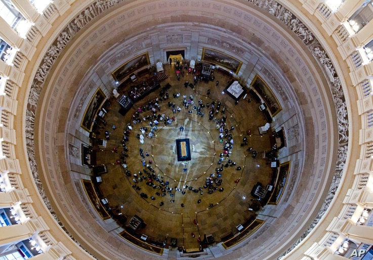 Visitors pay their respects as the casket of Reverend Billy Graham lies in honor at the Rotunda of the U.S. Capitol Building in Washington, Feb. 28, 2018.