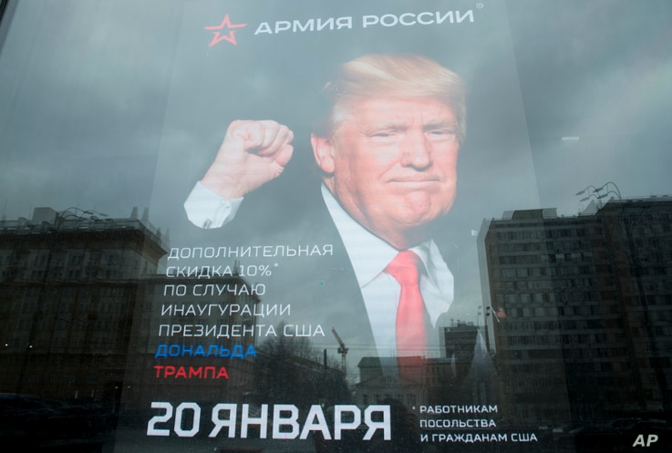"""The U.S. Embassy building is reflected in a window of a Russian military outerwear shop """"Armia Rossii"""" (Russian Army) displaying a poster of U.S. President Donald Trump, in downtown Moscow, Russia, Jan. 20, 2017."""