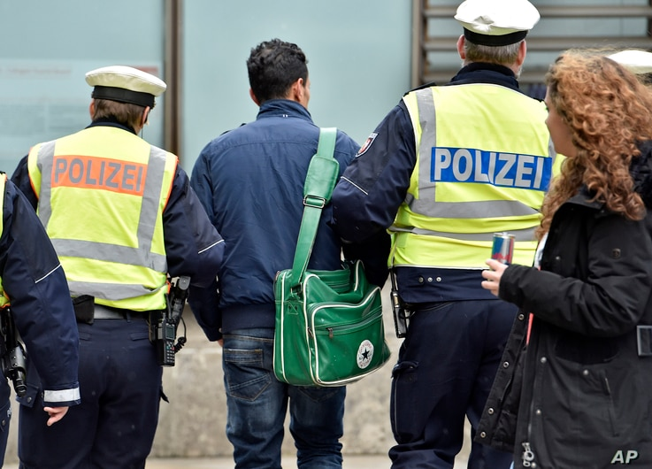 Police lead away a man at the main train station, Jan. 12, 2016, in Cologne, Germany. New Year's Eve sexual assaults and robberies in Cologne were blamed largely on foreigners and pushed the discussion about the migration crisis.