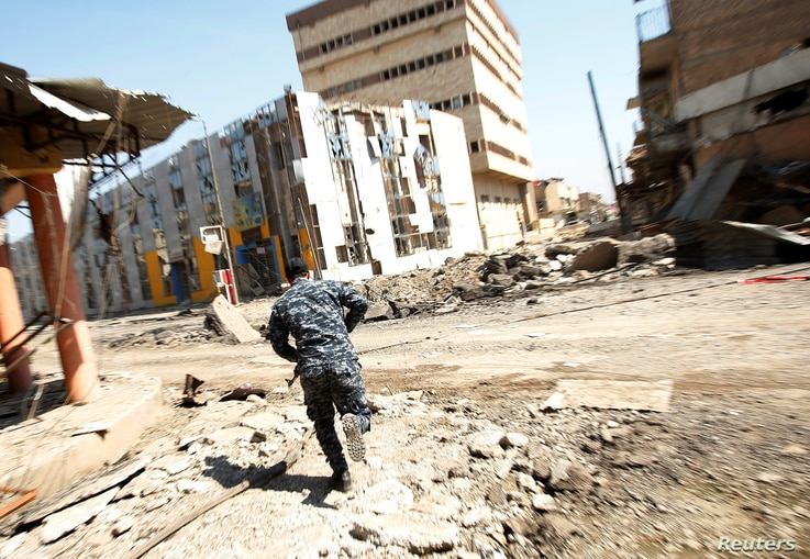 Iraqi Federal Police take cover during a battle with Islamic State fighters at Bab al-Jadid district in the old city of Mosul, March 26, 2017.