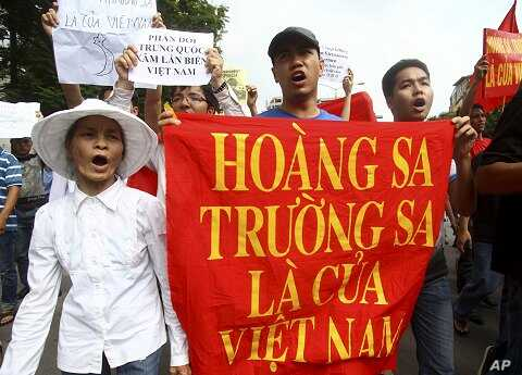 "Vietnamese protesters carry a banner with a Vietnamese slogan reading, ""Paracel islands and Spratly islands belong to Vietnam,"" during a protest demanding China to stay out of their waters following China's increased activities around the Spratly Isl"