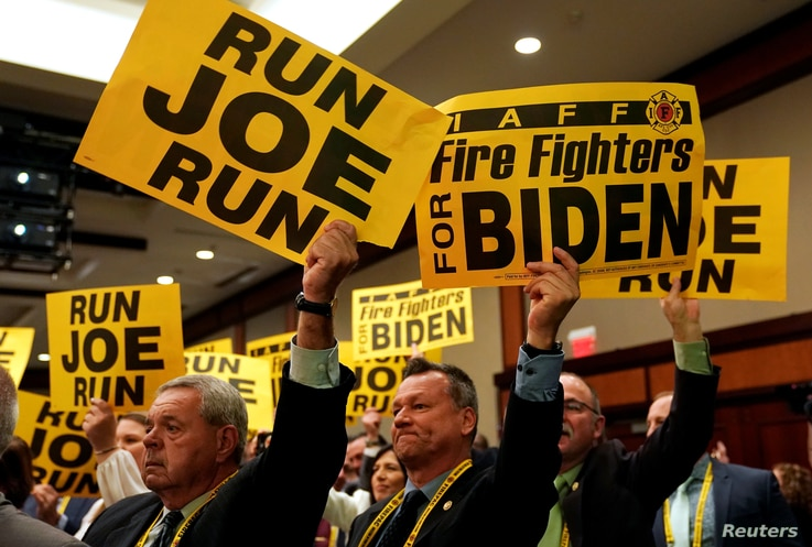 Supporters hold signs as former Vice President Joe Biden addresses the International Association of Fire Fighters in Washington, US, March 12, 2019.