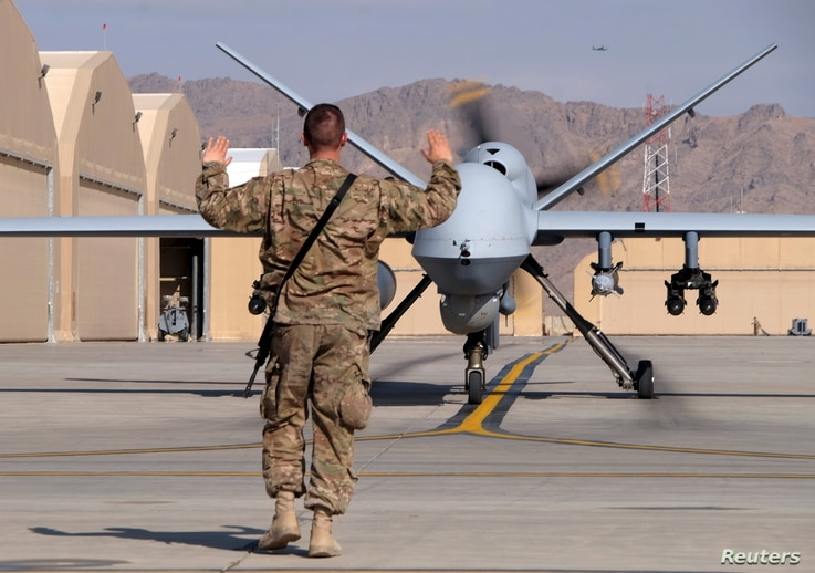 A US airman guides a US Air Force MQ-9 Reaper drone as it taxis to the runway at Kandahar Airfield, Afghanistan, March 9, 2016.