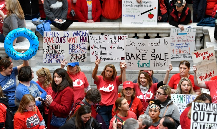 Teachers from across Kentucky hold up signs as they fill the state Capitol to rally for increased funding and to protest last-minute changes to their state-funded pension system, in Frankfort, Kentucky, April 2, 2018.