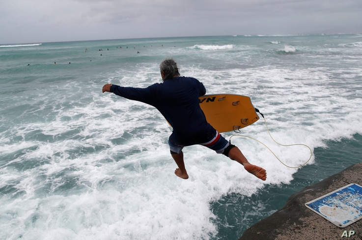 A bodyboarder jumps into the surf along Waikiki Beach ahead of Hurricane Lane, Aug. 24, 2018, in Honolulu. i