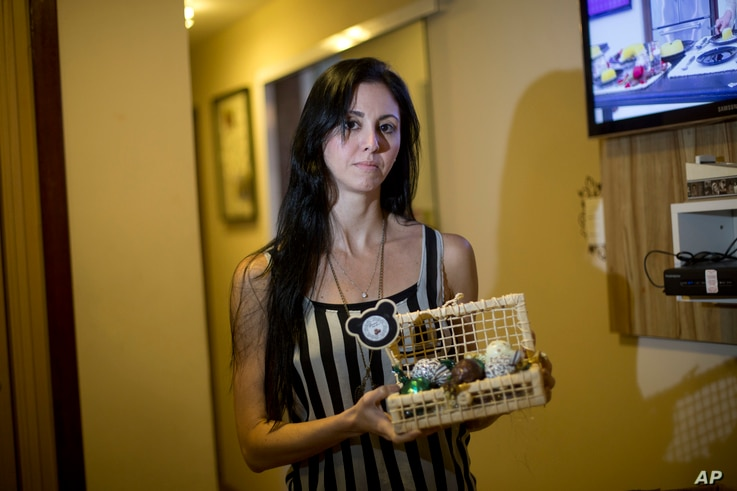 In this June 9, 2017 photo, Municipal Theatre of Rio de Janeiro ballet dancer Renata Gouveia shows truffles she sells to make ends meet in Rio de Janeiro, Brazil. Thousands of public workers are not being paid on time, or at all. Among them is the ba...