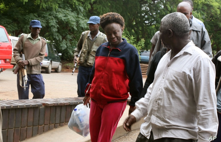 FILE - Zimbabwean human rights activist, Jestina Mukoko, center, is led into court in Harare, Zimbabwe Wednesday, Dec. 24, 2008.  State media report that Mukoko, who went missing three weeks ago, is accused of attempting to recruit government opponen...