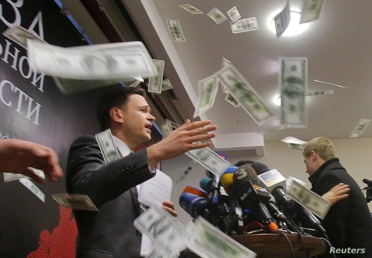 An unidentified person throws pieces of paper, resembling banknotes, as Russian opposition figure Ilya Yashin (L) presents his report, titled 'National Security Threat' and dedicated to current situation in Chechnya and its leader Ramzan Kadyrov, in ...