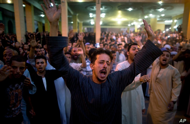 Coptic Christians shout slogans during a funeral service for victims of a bus attack, at Abu Garnous Cathedral in Minya, Egypt, May 26, 2017.