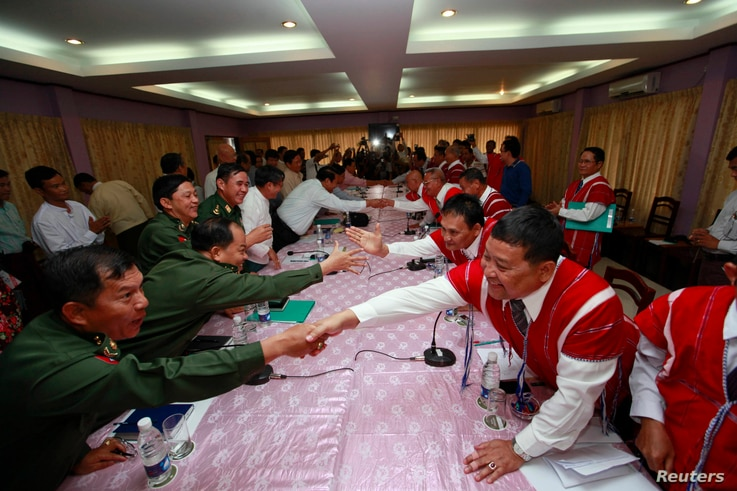 FILE - Representatives from Myanmar's government and the Karen National Union (KNU) shake hands during peace talks at Hotel Zwekabin in Pa-an, capital of the Karen State in eastern Myanmar, Jan. 12, 2012.