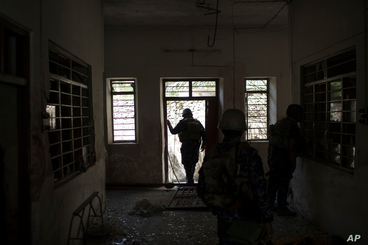 Federal policemen inspect the interior of a house as fighting against Islamic State militants continues on the western side of Mosul, Iraq,  March 29, 2017.