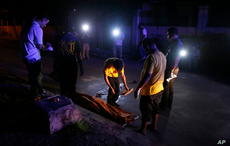 Funeral workers prepare to remove the body of a crime suspect after he was killed in gunbattles, Aug. 17, 2017 in Manila, Philippines.