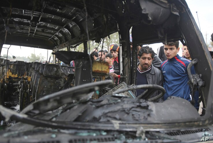 Citizens inspect the scene after a car bomb explosion at a crowded outdoor market in the Iraqi capital's eastern district of Sadr City, Iraq, Jan 2, 2017.