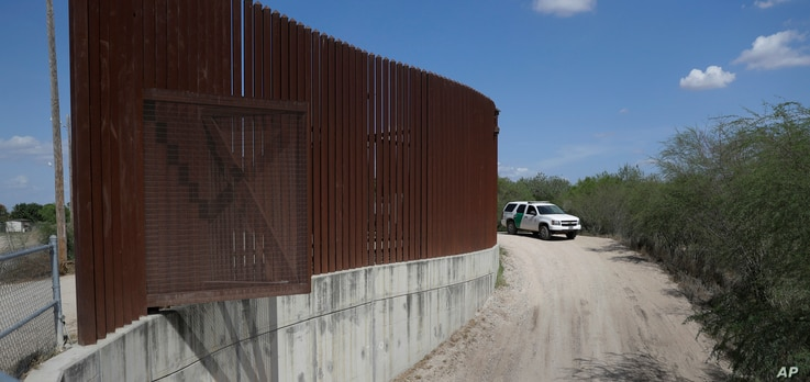 In this Aug. 11, 2017, file photo, a U.S. Customs and Border Patrol vehicle passes along a section of border levee wall in Hidalgo, Texas. The Department of Homeland Security  posted a waiver Oct. 10, 2018, that lists six sections where it plans to b...