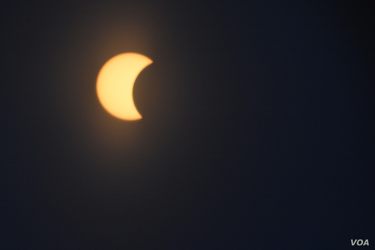 The moon is seen as it passes in front of the sun during a partial solar eclipse in Washington, D.C., Monday, Aug. 21, 2017. (Diaa Bekheet/VOA)