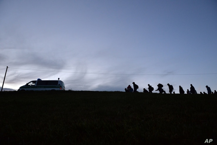 German federal police officers guide a group of migrants on their way after crossing the border between Austria and Germany in Wegscheid near Passau, Germany, Oct. 28, 2015.