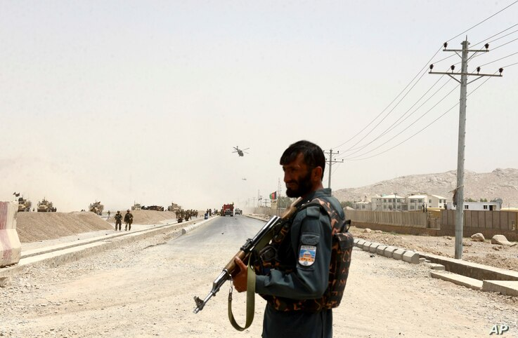 An Afghan policeman stands guard near the site of a suicide bomb attack on a NATO convoy in Kandahar, south of Kabul, Afghanistan, Aug. 2, 2017.