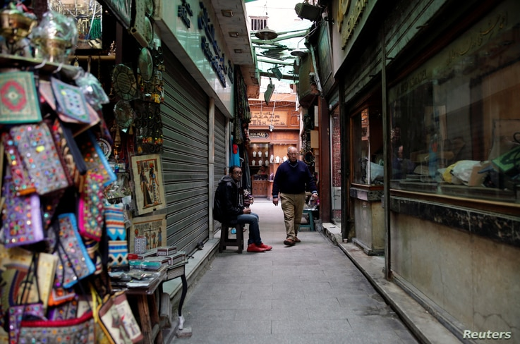 """A shopkeeper waits for tourists near rows of closed shops at a popular tourist area named """"Khan el-Khalili"""" in the al-Hussein and Al-Azhar districts in old Islamic Cairo, Egypt, Feb. 23, 2017."""
