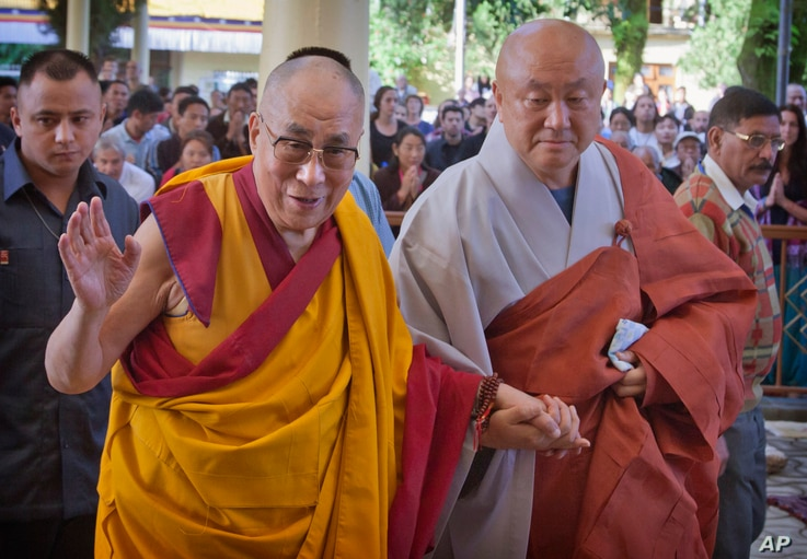 FILE - Tibetan spiritual leader the Dalai Lama, left, greets devotees as he arrives to give a talk at the Tsuglakhang temple in Dharmsala, India, Sept. 7, 2015.