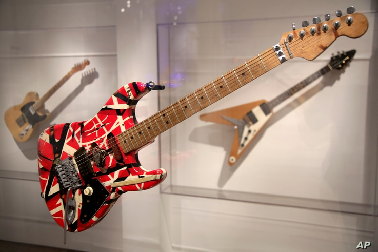 """A guitar made and played by Eddie Van Halen of Van Halen is displayed at the exhibit """"Play It Loud: Instruments of Rock & Roll"""" at the Metropolitan Museum of Art in New York, April 1, 2019."""