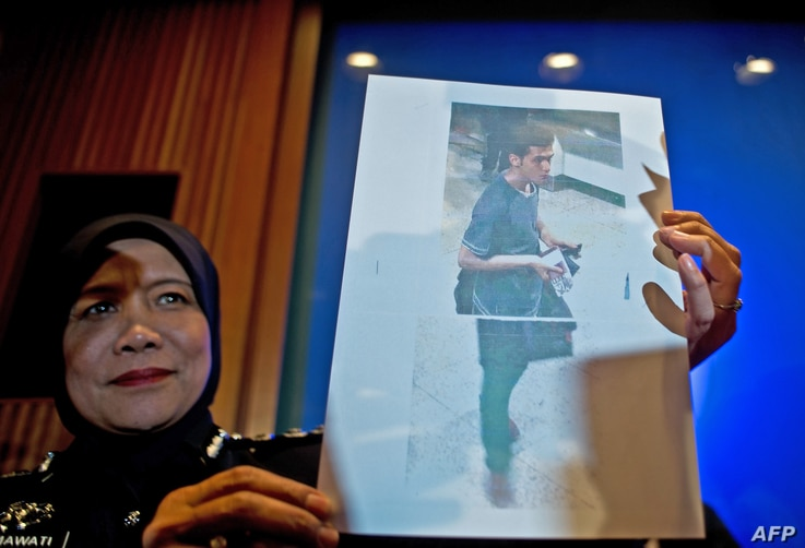 A Malaysian police official displays a photograph of 19-year-old Iranian Pouria Nour Mohammad Mehrdad, one of the two men who boarded missing Malaysia Airlines MH370 flight using stolen European passports to the media at a press conference near Kuala...