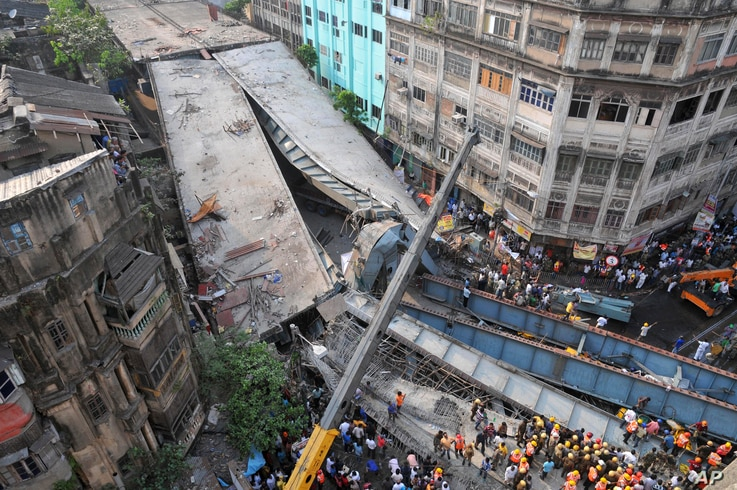 Locals and rescue workers clear the rubbles of a partially collapsed overpass in Kolkata, March 31, 2016.