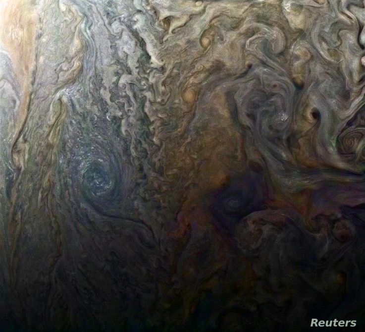 """NASA's enhanced-color image of a mysterious dark spot on Jupiter shows a Jovian """"galaxy"""" of swirling storms in this image captured by NASA's Juno spacecraft, Feb. 2, 2017, at an altitude of 9,000 miles (14,500 kilometers) above Jupiter's cloud tops. ..."""