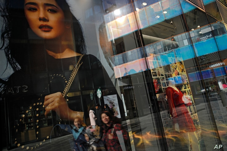Chinese shoppers are reflected on a fashion boutique's window panels as they walk through the capital city's popular shopping mall in Beijing, Friday, Feb. 1, 2019.
