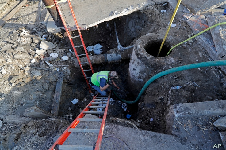 Workers fix a sewer main below the sidewalk in Mid City New Orleans, Jan. 31, 2018. City officials say New Orleans needs more than $11 billion to update key parts of its infrastructure but has about $2 billion in hand.