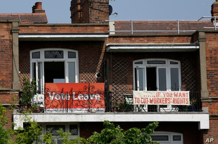 FILE - Banners of opposing views on Britain's Brexit referendum on continued EU membership are displayed on the balconies of two neighboring apartments in the Gospel Oak area of north London, Briatin, May 27, 2016.