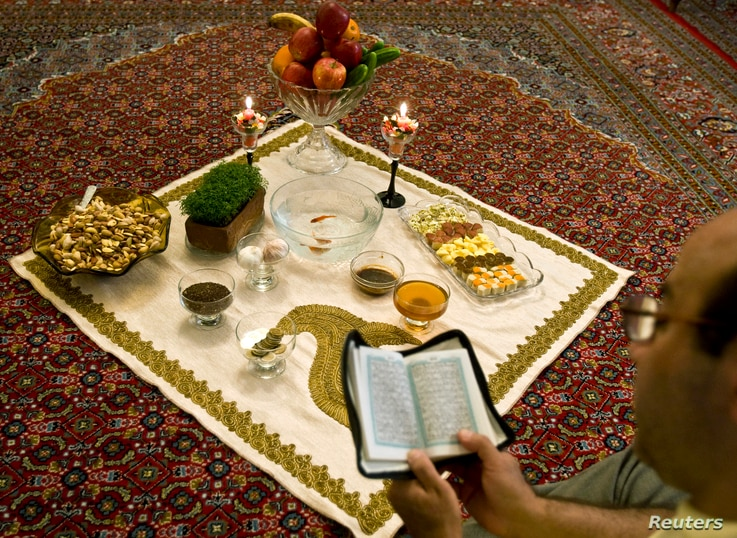 An Iranian man reads the Koran beside a traditional table 'Haft Seen' or 'Seven S', before the start of the Nowruz, or the Iranian New Year in Tehran March 20, 2009.