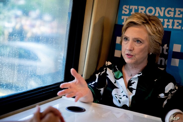 Democratic presidential candidate Hillary Clinton speaks on her campaign bus after visiting Imani Temple Ministries in Cleveland, 2016.