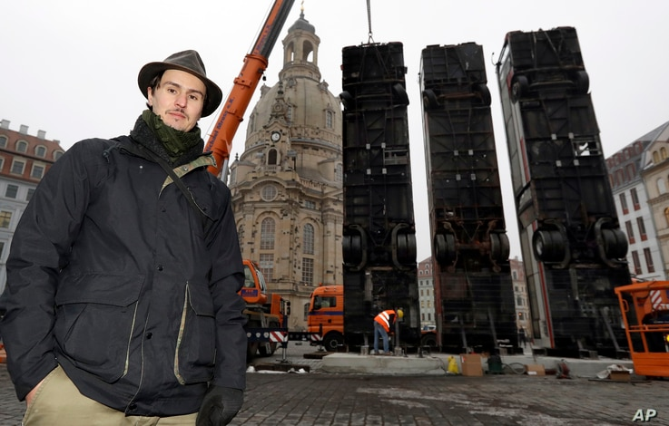 Syrian artist Manaf Halbouni poses in front of three busses close to the 'Frauenkirche' church in the center of the east German city of Dresden, Germany, Feb. 6, 2017.
