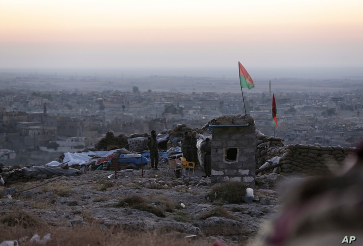 Kurdish fighters watch in the early morning as they fight against the Islamic State group in Sinjar, Iraq, Friday, Nov. 13, 2015.