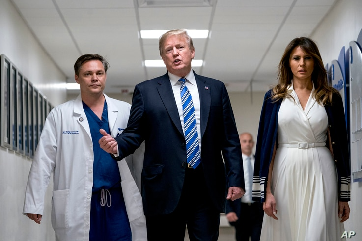 President Donald Trump, center, accompanied by first lady Melania Trump, right, and Dr. Igor Nichiporenko, left, speak to reporters while visiting with medical staff at Broward Health North in Pompano Beach, Fla., Feb. 16, 2018.