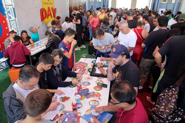 FILE - Collectors exchange World Cup stickers for their albums at a trading event outside the Pacaembu stadium in Sao Paulo, Brazil, May 26, 2018.