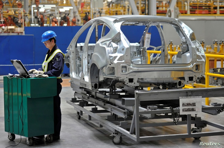 FILE - An employee uses a laptop next to a car body at an assembly line at a Ford manufacturing plant in Chongqing municipality, April 20, 2012.