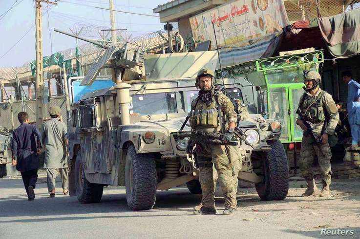 Afghan security forces keep watch in front of their armoured vehicle in Kunduz city, Afghanistan, Oct. 4, 2016.