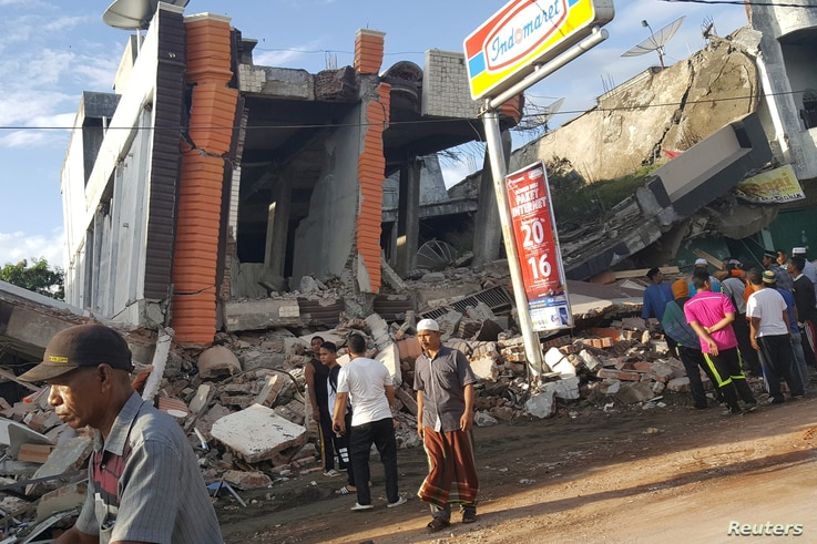 People survey the damage after dozens of buildings collapsed following an earthquake in Ule Glee, Pidie Jaya in the northern province of Aceh, Indonesia, Dec. 7, 2016.