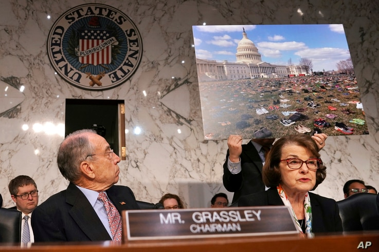 Senate Judiciary Committee Chair Sen. Chuck Grassley, R-Iowa, left, looks at a poster of 7,000 pairs of shoes that were displayed outside the Capitol Tuesday to represent victims of gun violence since the shootings at Sandy Hook Elementary School, as...