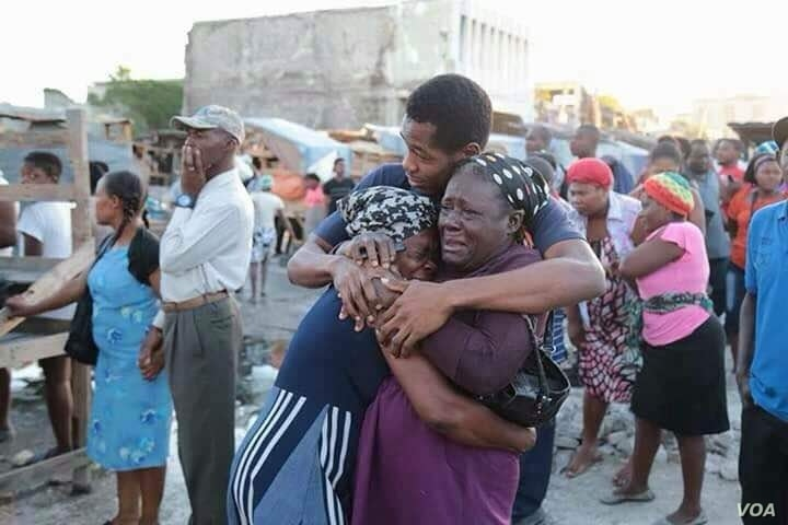 Vendors who lost merchandise in the Iron Market fire console each other after arriving on the scene, Feb. 13, 2018. (R.M. Givens/VOA Creole)