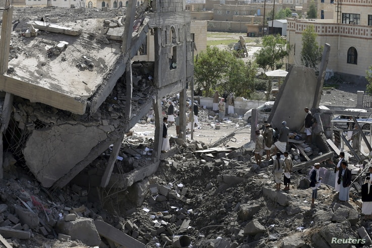Houthi militants gather on the rubble of the offices of the education ministry's workers union, destroyed by Saudi-led air strikes, in Yemen's northwestern city of Amran, August 19, 2015.
