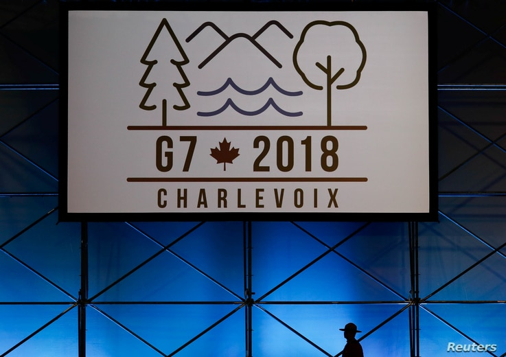 A Canadian mounted police officer walks past the Charlevoix G7 logo at the main press center, ahead of G7 Summit in Quebec, Canada, June 6, 2018.