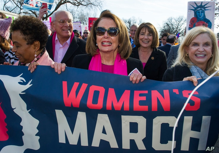 House Minority Leader Nancy Pelosi, D-Calif., center, Rep. Susan Davis, D-Calif, background center right, and Rep. Carolyn Maloney, D-N.Y., right, participate in the Women's March walk to the White House in Washington, Jan. 20, 2018. On the annivers...